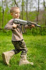 Boy carrying a machine gun saluting