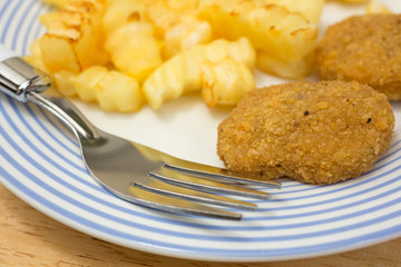 Chicken nuggets with french fries and fork on table