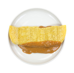 Corn tortilla filled with peanut butter on plate