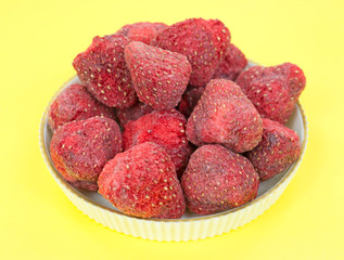 Dehydrated strawberries in a bowl on a yellow background