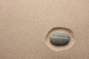 Striped gray stone lying in the sand