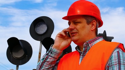 Railroad worker with cell phone near signal beacons