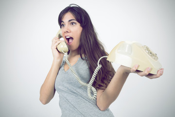 Surprised girl with retro phone