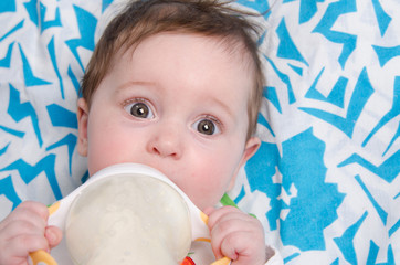 Six-month girl drinking milk formula from a bottle