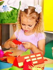 Child girl  glue in preschool.