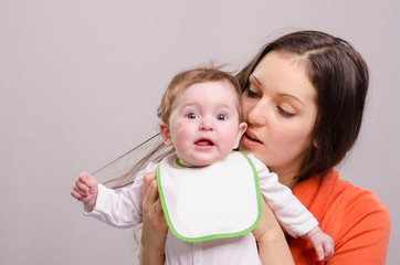 Six-month baby girl in bib tear your hair mom