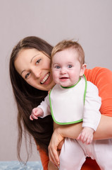 Young happy mother hugging baby girl in bib