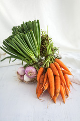 Carrots on wooden background and white fabric