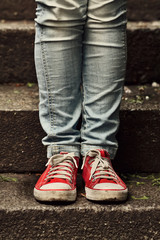 Little girl in red sneakers and jeans standing on the stairs
