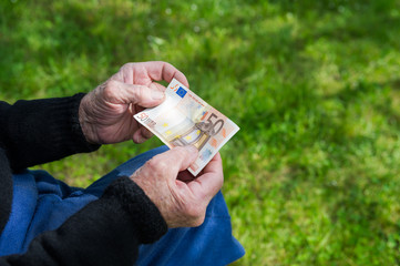 Senior man's hands holding Euro banknote. Struggling pensioners