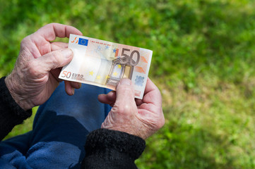 Senior man's hands holding Euro banknote. Struggling pensioner