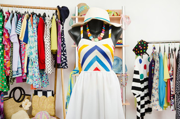 Wardrobe with summer clothes and a beach outfit on a mannequin.