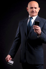 old businessman with credit card and mobile