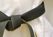 Karate Black Belt on White Uniform - 65948917