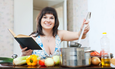 Woman cooking with cookbook