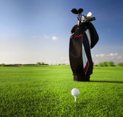Golf clubs in golfbag and golf balls green grass background