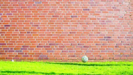 soccer ball near a brick wall