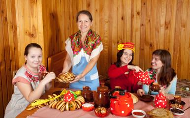 Women  drinks tea and eats pancakes