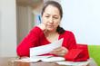 mature woman reads bills