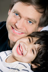 Handsome young father smiling with disabled little son