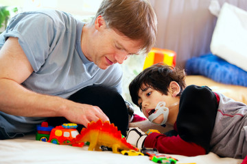 Handsome father playing cars with disabled son