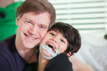 Smiling father holding disabled son