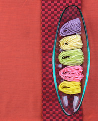 Colorful dry noodles in glass tray on red cloth background