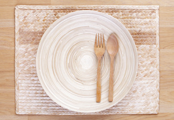 wooden spoon and fork and empty wooden dish on bamboo napery