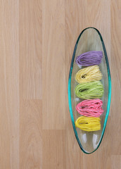 Colorful dry noodles in glass tray on wooden background
