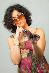 Ragazza indecisa e dubbiosa che prova degli occhiali