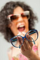 Ragazza che urla tenendo degli occhiali da vista blu in mano