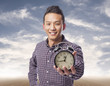 portrait of young asian man holding an alarm clock