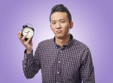 portrait of young asian man demotivated holding an alarm clock poster