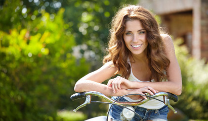 beautiful summer woman next to the bike
