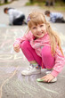 Cute little girl drawing with chalk outdoors