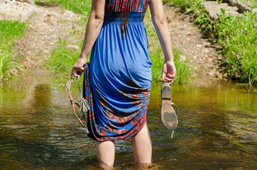 girl holds sandals wade barefoot flowing stream