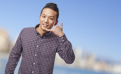 young chinese man doing a call gesture