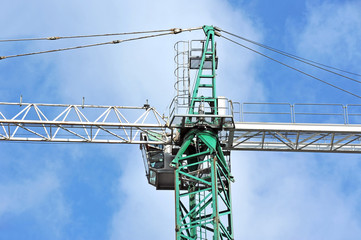 Green construction tower crane against blue sky