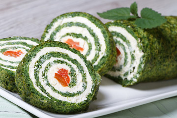 Roll spinach and cream cheese closeup on white plate