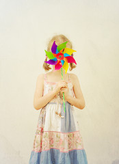 Little girl hides behind colorful pinwheel. Vintage effect.