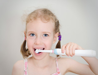 Little girl brushing her teeth with electric toothbrush.