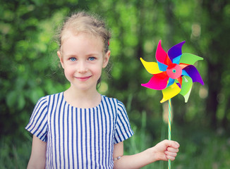 Little girl with colorful pinwheel in the park.