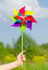 Child hand holding pinwheel against blue sky.