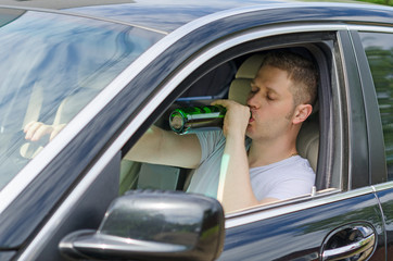 Driving Under the Influence. Man drinking alcohol in the car.