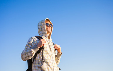 Happy man hiker holding backpack on a sunny day