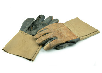 A dirty and well-worn pair of canvas and leather work gloves on