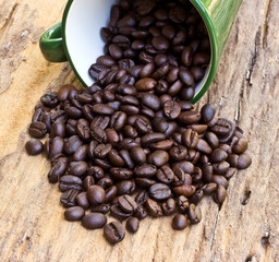 A Cup of coffee beans is on wooden board