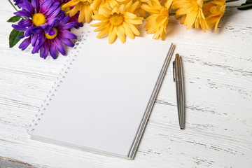 Notebook, pen and flowers on the table