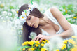 Young beautiful woman lying on a meadow of dandelions