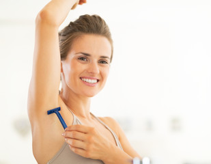 Portrait of happy young woman shaving armpit